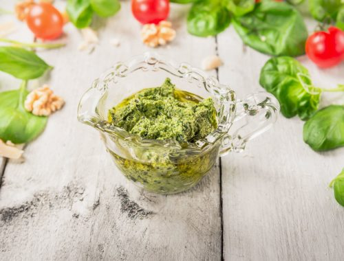 basil pesto in glass cup over tomatoes, walnut and parmesan on white wooden background